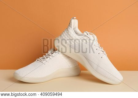 Pair Of Stylish Sport Shoes On Orange Background