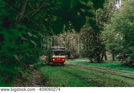 The Tram Goes Through Dense Thickets Of Trees. Summer Landscape In The Park With The Tram. Izhevsk,