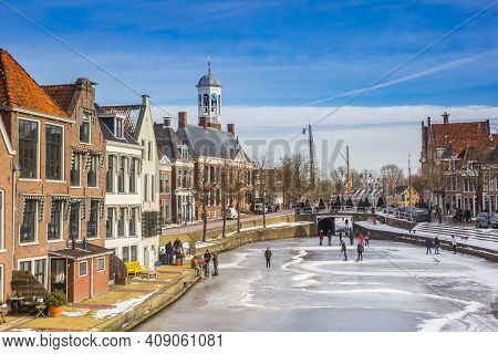 Dokkum, Netherlands - February 14, 2021: Old Houses And Town Hall In A Typical Dutch Winter Scene Wi
