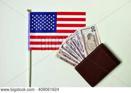 American Flag And Dollar Bills In Wallet On Green Background. Studio Photography Of American Nationa