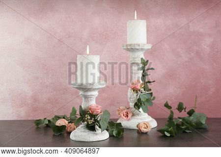 Vintage Candlesticks With Burning Candles, Roses And Eucalyptus On Table