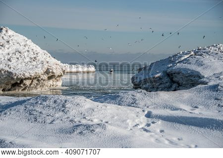 Lake Michigan Shoreline In Winter With Mounds Of Snow And Ice Inlet With Birds Flying Above Overhead