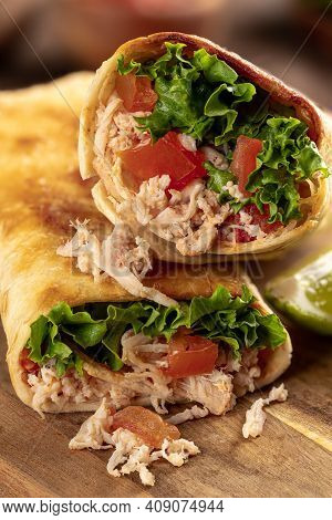 Closeup Of Two Chicken Burritos With Lettuce And Tomato On A Wooden Cutting Board