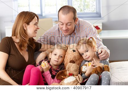 Happy family with two daughters and pregnant mother sitting on sofa.