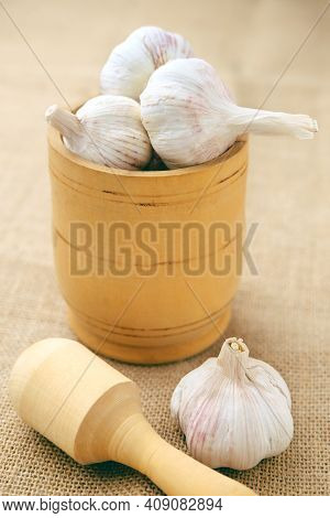 The Garlic Bulbs Are In A Wooden Bowl, With A Crush Next To It.