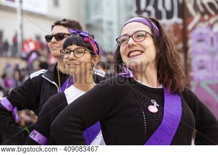 Madrid, Spain - March 8, 2019: Young Women Dressed In Scarves And Violet Sash Smiling During The Man