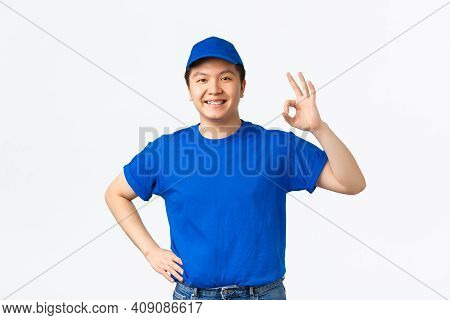 Smiling Confident Asian Courier In Blue Uniform, Wink And Showing Okay Gesture. Delivery Guy Say Ok,