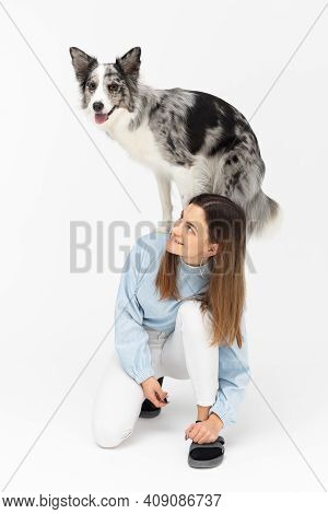 The Dog Is Standing On The Back Of Its Owner. Young Adult Girl. Border Collie Dog. A Purebred Dog Wi