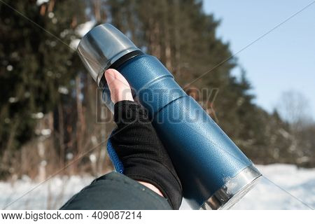 Male Hand In A Glove Showing A Thermos Outside. First-person Perspective. Sunny Day, Winter Snowy Fo
