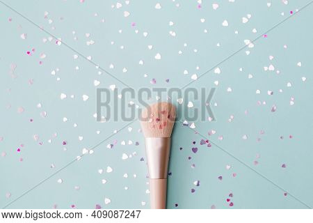 Makeup Brush And Shiny Sparkles Confetti In Shape Of A Heart On Pastel Blue Background. Festive Make