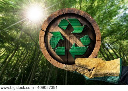 Hand With Protective Work Glove Showing A Recycling Symbol Made Of Green And Brown Wood Inside Of A
