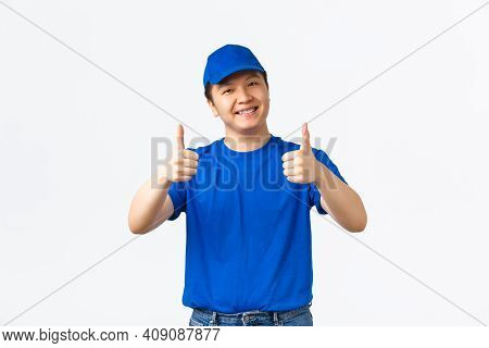 Friendly Smiling Asian Delivery Guy In Blue Uniform, Cap And T-shirt, Showing Thumbs-up In Approval,