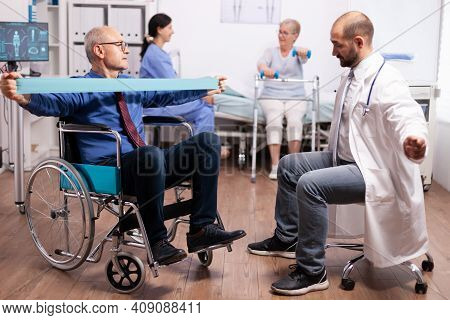 Disabled Senior Man Being Assisted By Physical Therapist By Doctor In Modern Heathcare Facility. Eld
