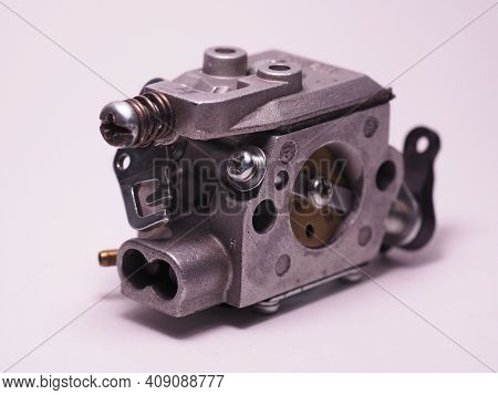 Chainsaw Carburetor On A White Background. Chainsaw Spare Part. Carburettor Adjustment