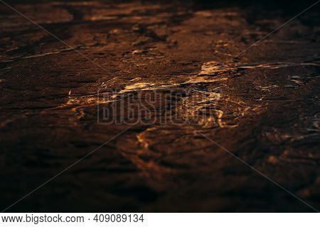 Glowing Sandy Cracks With Golden Water Running Through Crevices At Sunset.