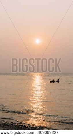 Two People Kayak In One Boat During Beautiful Orange Sunset In Koh Samet, Thailand.