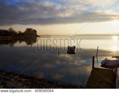 Magical Tranuil Beautiful With Clear Calm Water Sunset With Great Clouds Formation By The Sea Shore