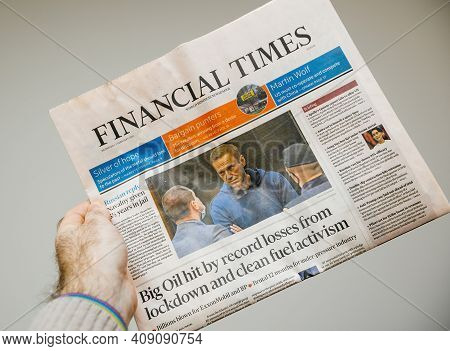 Paris, France - Feb 4, 2021: Pov Male Hand Holding Lates Financial Times Newspaper Reading About Nav