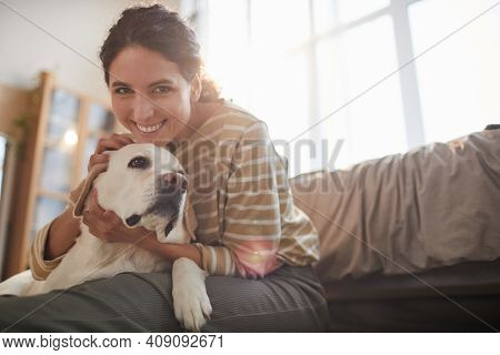 Portrait Of Smiling Young Woman Hugging Dog While Sitting On Floor In Cozy Home Interior Lit By Sunl