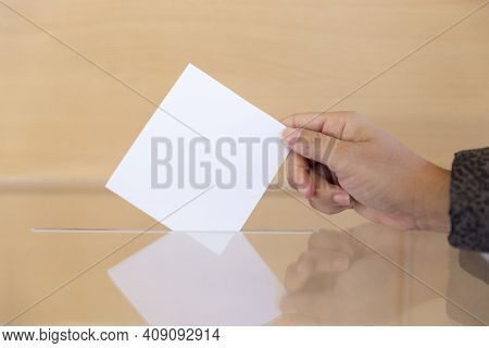 Close Up Of A Person\'s Hand Inserting A Blank Envelope Into A Ballot Box. Space For Text.