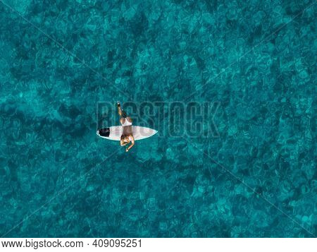 Surfer Woman With Surfboard In Blue Ocean. Aerial View With Surf Girl