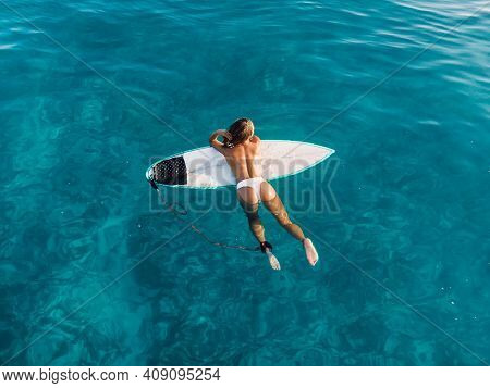 Attractive Surfer Woman Relaxing On Surfboard In Blue Ocean. Aerial View With Surf Girl