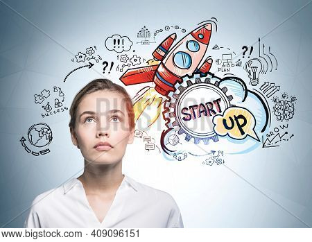 Attractive Business Woman Looking Up And Pondering About Start Up And How To Succeed On It. Concept