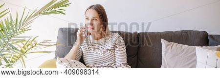 Pensive Middle Age Woman Talking On Mobile Phone. Young Sad Thinking Woman Sitting On Couch Sofa At