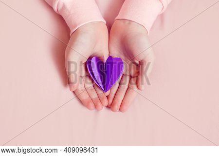 International World Epilepsy Illness Awareness Day. Kid Girl Hands Holding Small Violet Purple Paper