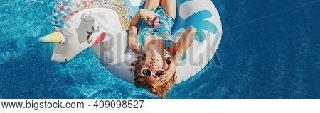 Cute Adorable Girl In Sunglasses With Drink Lying On Inflatable Ring Unicorn. Kid Child Enjoying Hav