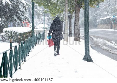 A Woman Walks Along A Snowy Street During A Snowstorm In The City Of Athens, Greece, 15th Of Februar