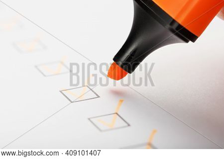 Orange Marker With Markers On The Checklist Sheet.