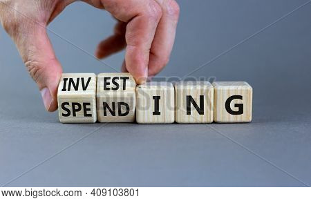 Spending Or Investing Symbol. Businessman Turns Cubes And Changes The Word 'investing' To 'spending'