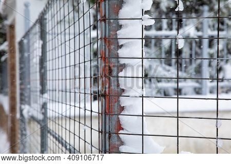 A Snow-covered Metal Lattice Fence With Dangerous Acute Corner Painted In Red - Abstract Background.