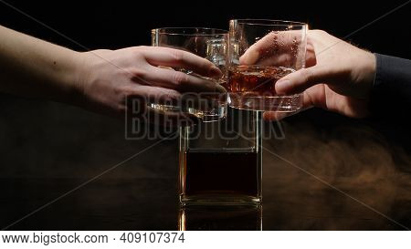 Two Hands With Glasses Of Cognac Whiskey With Ice Cubes Making Cheers On Black Background. Celebrati