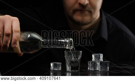 Bartender Man Pouring Up Frozen Vodka Or Sake From Bottle Into Shot Glass With Ice Cubes On Black Ba