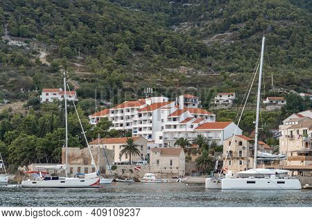 Komiza, Croatia - Aug 17, 2020: Catamarans And Yachts Parked On Old Town Shore On Vis Island In Summ