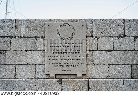 Komiza, Croatia - Aug 17, 2020: Stele On Stone Wall In Memory Of British Seamen On Vis Island Old Po