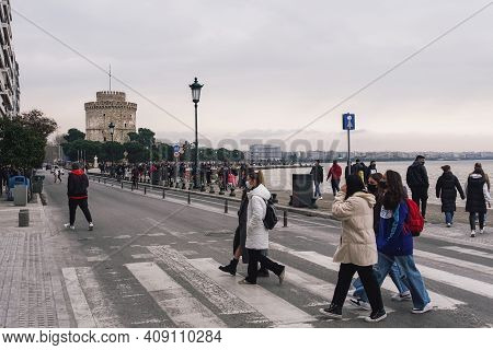 Thessaloniki, Greece - February 20 2021: People With Covid-19 Masks Before The City Landmark. Uniden