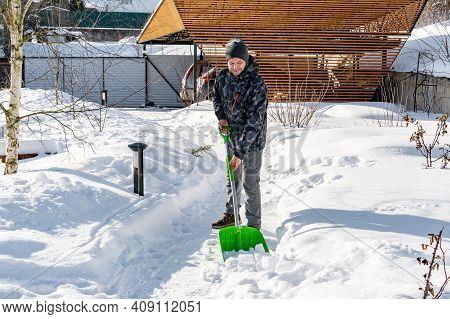 The Yard Was Covered With Snow After A Heavy Snowfall. A Man Cleans The Garden Paths From Snow On A