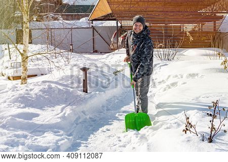 Smiling Man Cleans The Path From Snow With A Shovel. Cleaning The Garden From Snow After A Heavy Sno