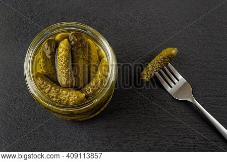 Open Glass Jar Of Tasty Pickled Gherkins And One More On The Spoon Against Black Slate Background. W