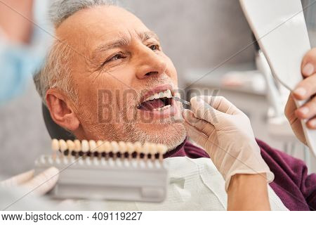 Dentist Using Tooth Color Chart To Patient