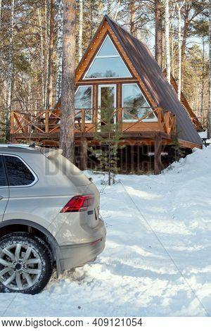 Back of the car of silver color standing in snowdrift in front of camera on background of country house in the forest on winter weekend