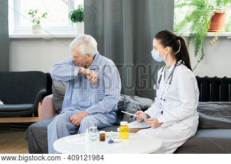 Young female general practitioner with touchpad looking at sick senior man going to cough or sneeze while sitting on couch in front of her
