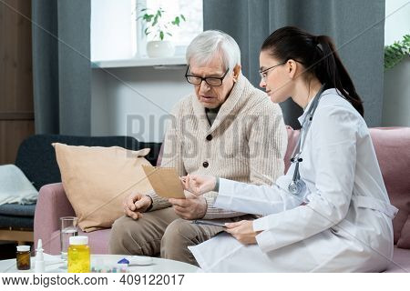 Young pretty brunette general practitioner pointing at paper with her recommendations while consulting sick senior man in living-room