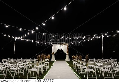 Beautiful Night Stage For The Wedding Ceremony. Wedding Wooden Arch. Stylish Wedding Decor. Chairs F