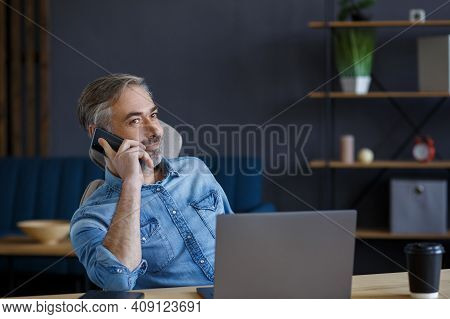 Senior Grey-haired Businessman Talking On The Phone In Office. Conversation With Business Partners.