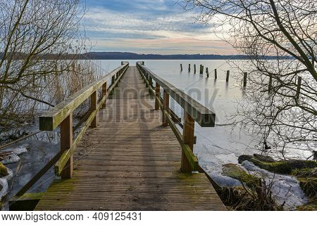 Wooden Footbridge Jetty On The Frozen Lake Of Ratzeburg, Last Winter Days In Early Spring, Landscape