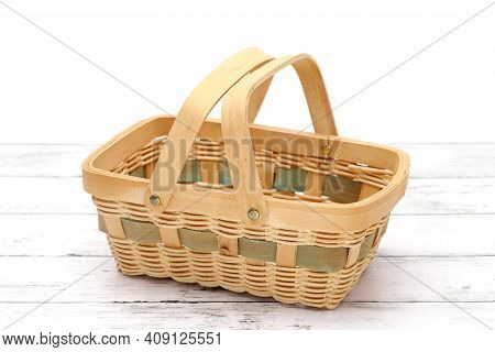Empty Bamboo Basket On A White Wooden Table